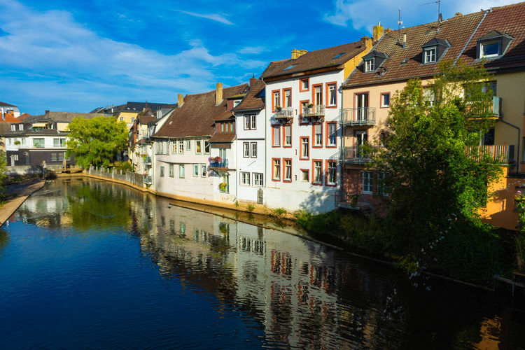 Houses by river in town against sky