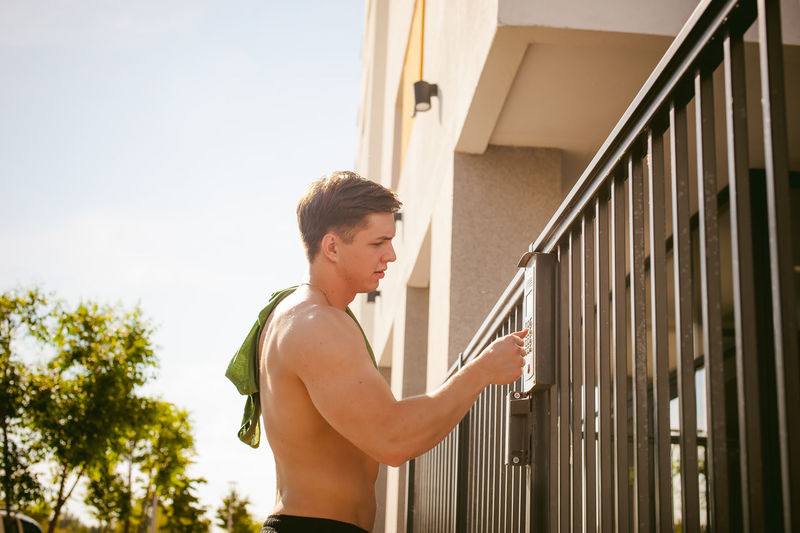 Shirtless man using gate intercom against sky