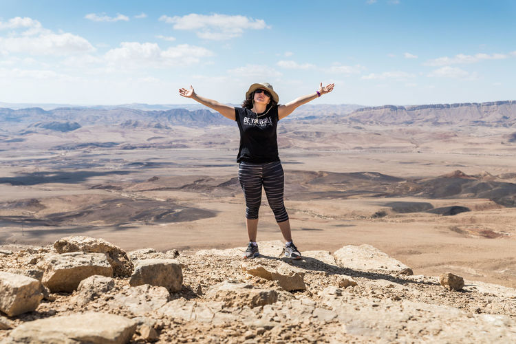 A young woman stands widely spreading her hands on the edge of the cliff against the background of the Judean Desert in Israel Israel Happiness Light Standing Background Beauty In Nature Blue Color Day Edge Of Cliff Judean Desert Landscape Leisure Activity Lifestyles Mountain Nature One Person Scenics - Nature Sky Sun Sunlight Travel Destinations Vacation Widely Spreading Hands Young Woman