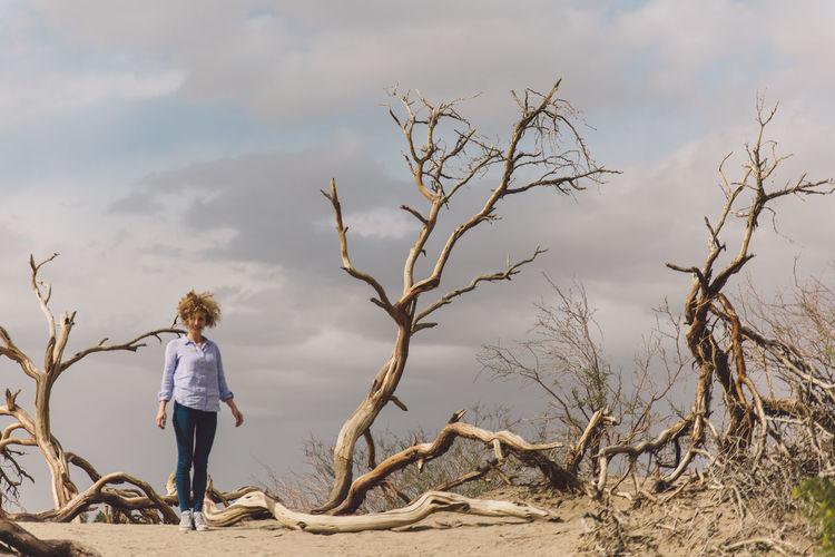Full length of woman standing on bare tree against sky