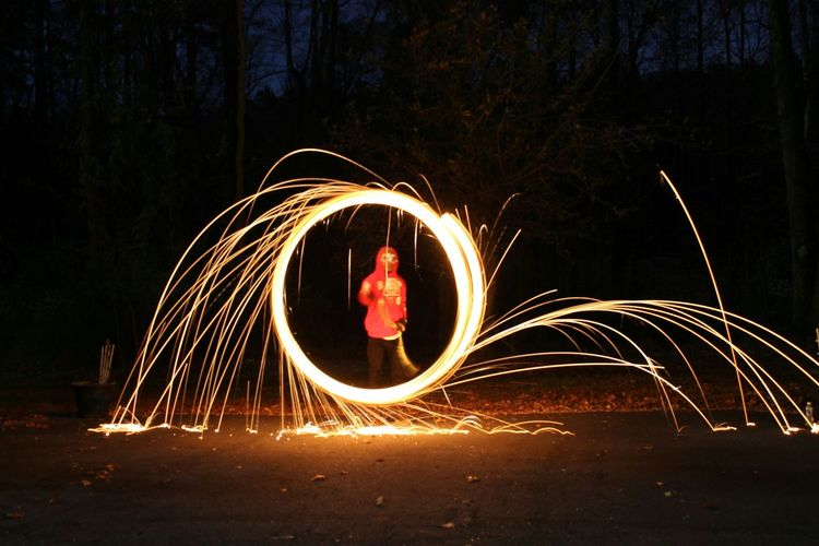 Person swinging illuminated wire wool on field at night