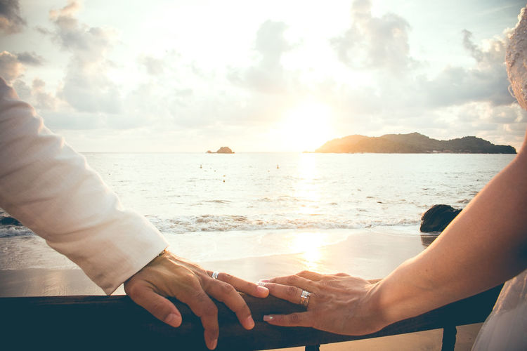 Midsection of couple kissing against sea