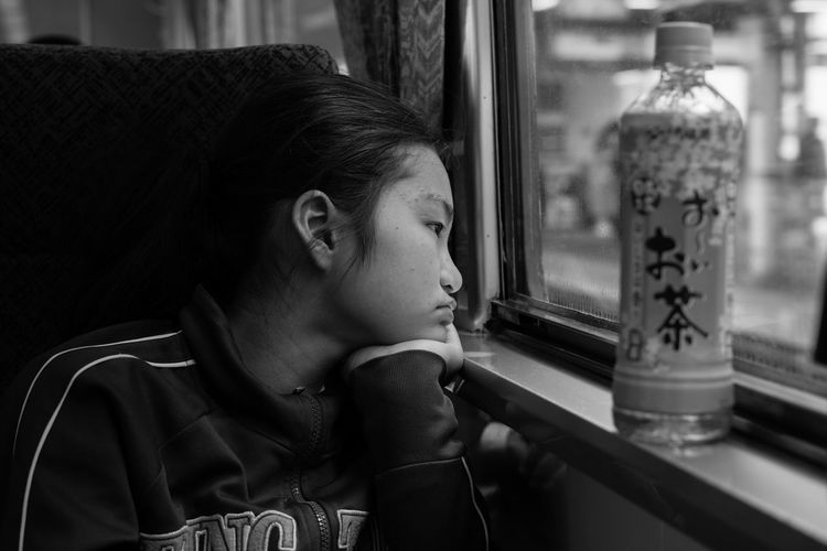 Girl looking through train window
