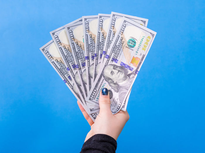 Woman hand with dollars isolated on blue background Benjamin Franklin Business Stories Currency Economy Franklin Hands Isolated Woman Blue Business Finance And Industry Dollars Finance Hundreds Money Savings