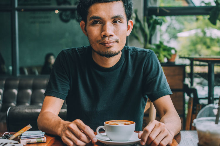 Portrait of young man drinking coffee in cafe