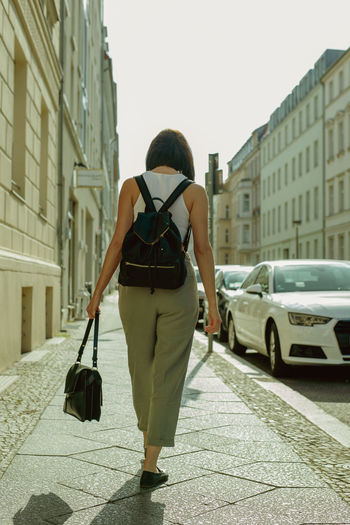 Rear view of woman walking on sidewalk in city during sunny day