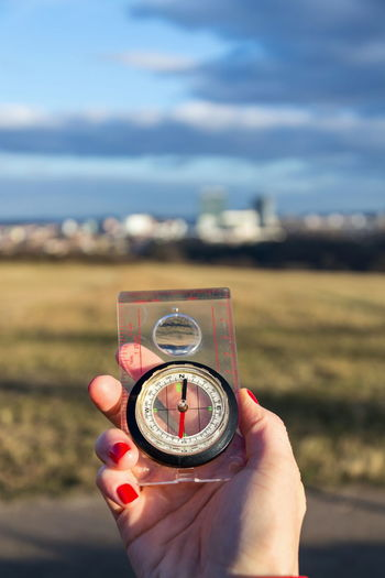 Cropped hand of woman holding navigational compass outdoors