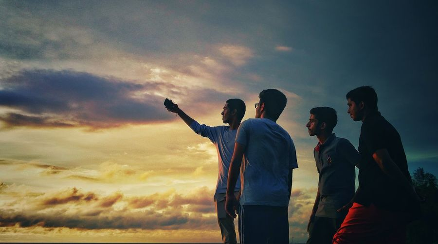 Friends taking selfie through mobile phone against sky