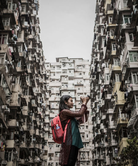 Low angle view of woman photographing while standing against buildings in city