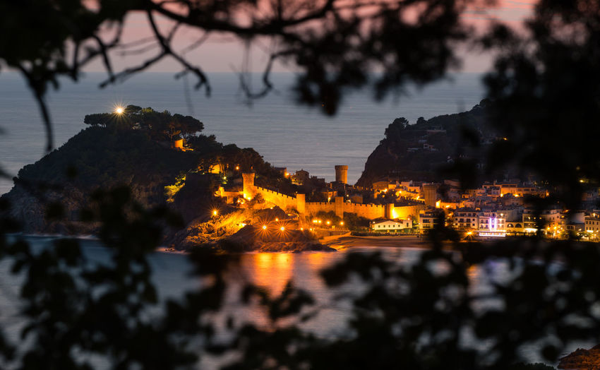 Illuminated City of Tossa de mar, Spain, and reflections of the ocean in blue hour after sunset Tree Water Illuminated Architecture Reflection Nature Silhouette City Night No People Sunset SPAIN Tossa De Mar Castle Lighthouse Costa Brava Catalunya Summer Vacations Long Exposure Blue Hour City Lights