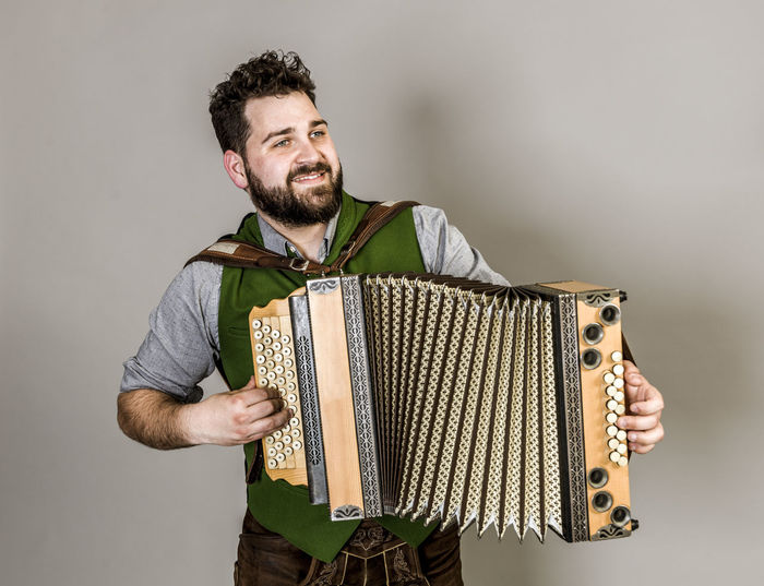 Musician Costume Leather Trousers Tradition Traditional Austria Green Pose Accordion Man Young Shorts Friendly Proud Happy Play Music Fun Joy Single One Background Copy Space Studio Entertainment Mountains Shirt STAND Hobby Leisure Cool Indoors  Young Adult Casual Clothing Standing One Person Smiling Three Quarter Length Young Men Holding Beard Studio Shot Real People Front View Looking Facial Hair Happiness Men Looking Away