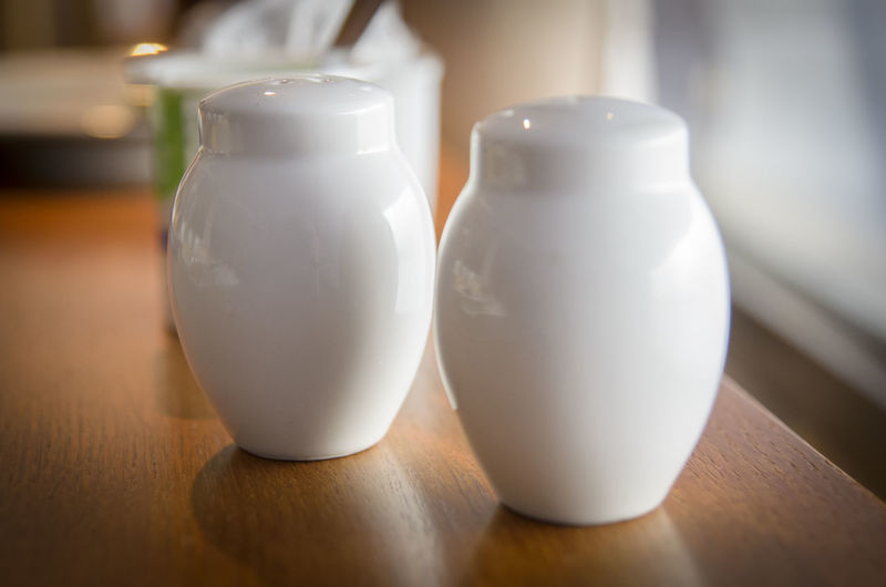 Close-up of salt and pepper shakers on table at home