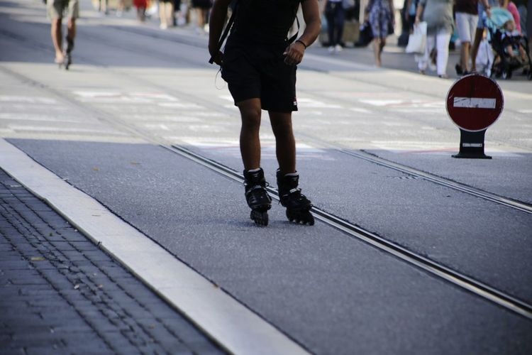 Low section of person skating on city street