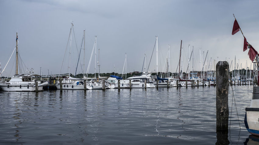 Cloud - Sky Day Flag Harbor Marina Mast Mode Of Transportation Moored Nature Nautical Vessel No People Outdoors Patriotism Pole Sailboat Sea Sky Transportation Water Waterfront Wooden Post Yacht