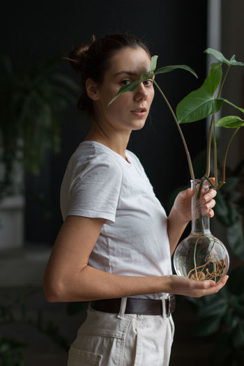 Young woman smiling while standing against plants