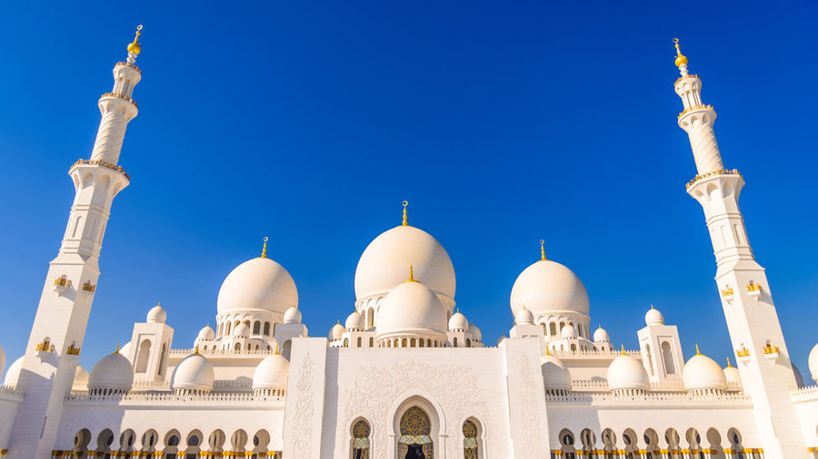 Low angle view of sheikh zayed mosque against clear blue sky