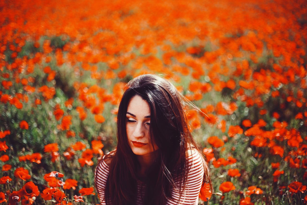 young adult, young women, real people, one person, nature, leisure activity, flower, lifestyles, beautiful woman, front view, outdoors, day, plant, focus on foreground, growth, beauty in nature, autumn, tree, adult, people