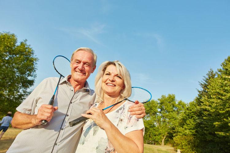 Portrait Of Senior Couple Holding Badminton Rackets At Park