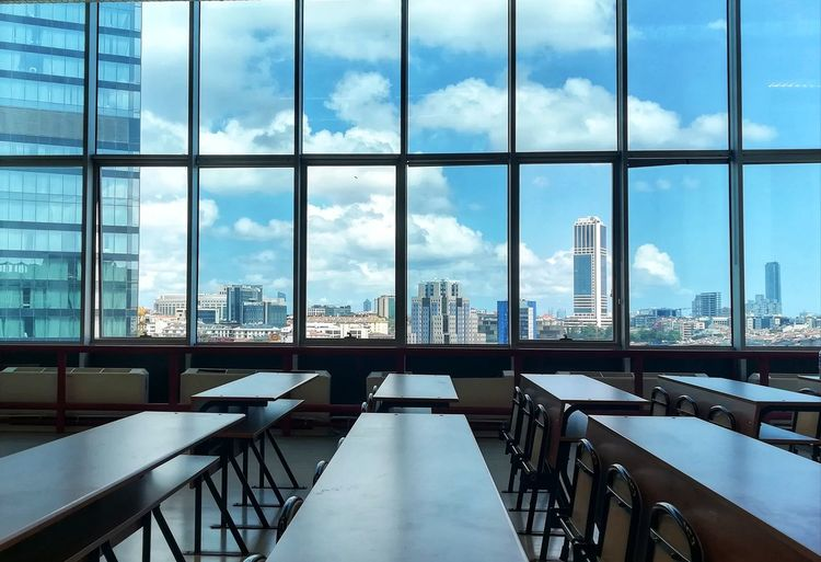 'My University's Window' 💙 Blue Clouds Window View Table School EyeEm Best Shots Day Sky City Cityscape Futuristic Urban Skyline Modern Skyscraper Business Space Business Finance And Industry Office Office Building Exterior Convention Center Tower Tall - High Building Story Office Building