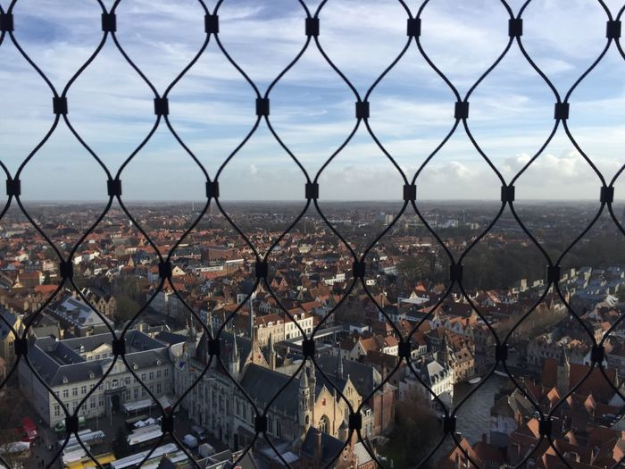 Close-Up Of Cityscape Seen Through Chainlink Fence