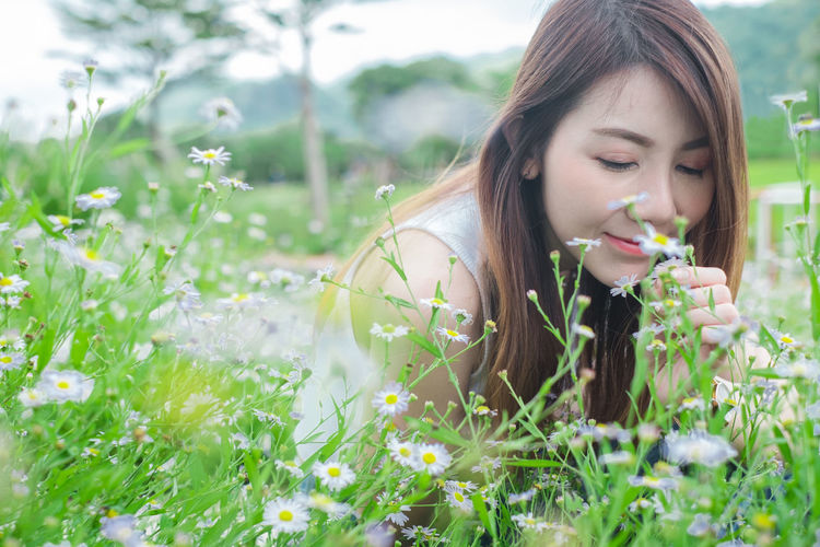 Beautiful young woman with flowers on field