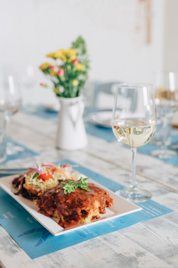 Greek style fish fillet with tomato sauce Cuisine Greek Meal Salad Tomato Sauce Fish Fish Fillet Focus On Foreground Food Food And Drink Glass Greek Food Indoors  Plate Ready-to-eat Recipe Still Life Table Traditional White Wine Wine Wineglass