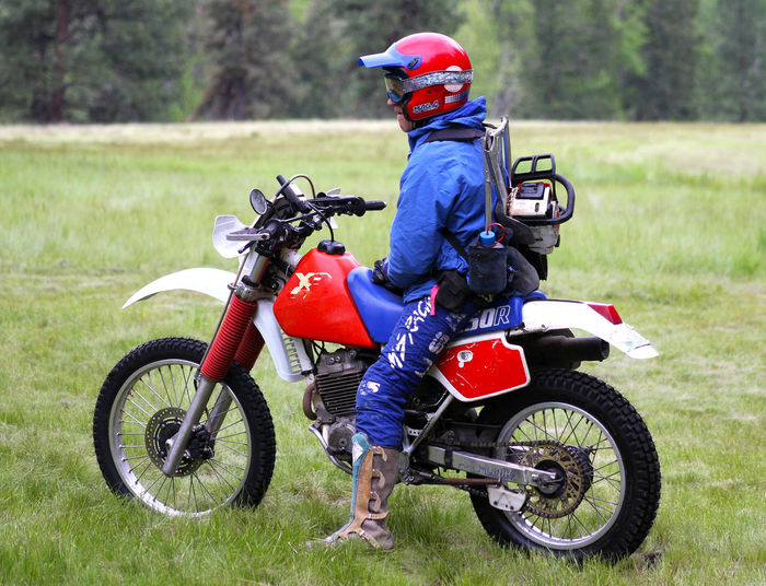 Blue Chainsaw Day Dirtbike Field Focus On Foreground Full Length Grass Grassy Helmet Land Vehicle Leisure Activity Lifestyles Mode Of Transport Motorbike Motorcycle Motorcycle On The Move Real Man Red Red White And Blue Riding Suited Up Transportation Travel Second Acts Be. Ready.