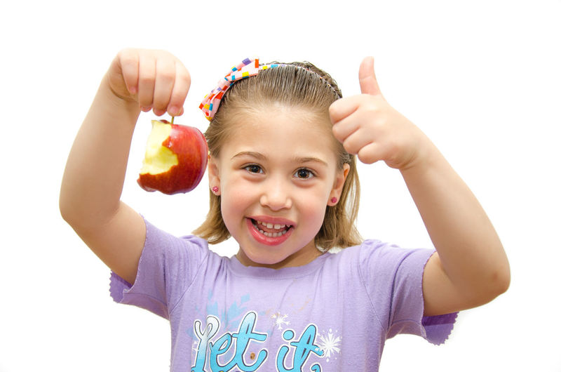 Happy girl holding apple while gesturing thumbs up sign against white background