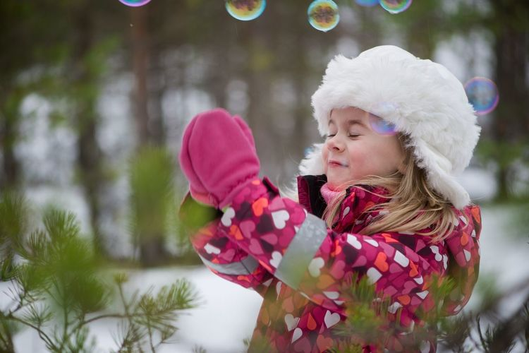 Close-up of girl with soap bubbles in winter