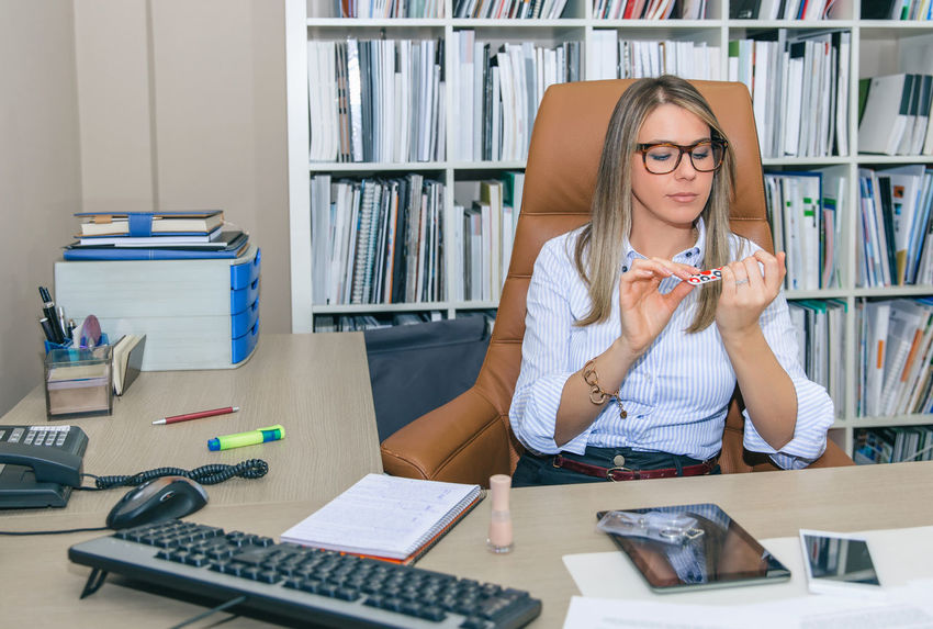 Portrait of bored blonde secretary polishing nails at workplace At Work Beautiful Blonde Business Company Desktop Horizontal Stress Teamwork Work Working Hard Workplace Business Finance And Industry Businesswoman Caucasian Computer Concentration Document Fold Headset Indoors  Long Hair Office Building One Person Talking