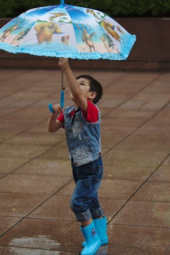 Nanjing Road Blue Blue Boots Boy Casual Clothing Childhood Enjoyment Full Length Fun Happiness Leisure Activity Lifestyles One Person Outdoors Playing Rain Real People Street Photography Umbrella Wet