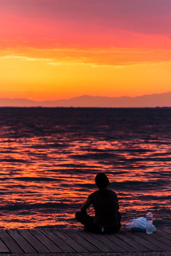 Rear view of silhouette man sitting on sea against orange sky