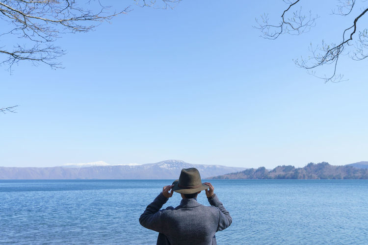 Rear view of man wearing looking at lake against clear sky