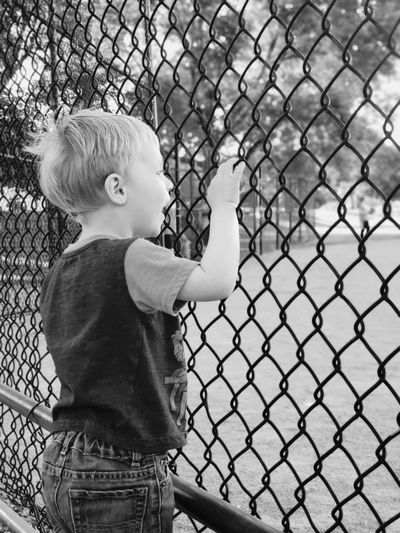 Boy looking through chainlink fence