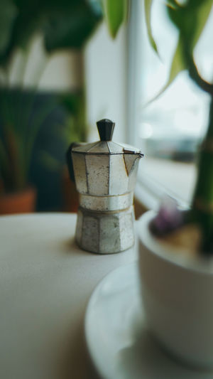 Coffee pot on table by window