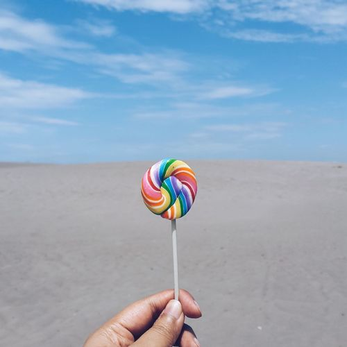 Cropped image of hand holding colorful lollipop at beach against sky