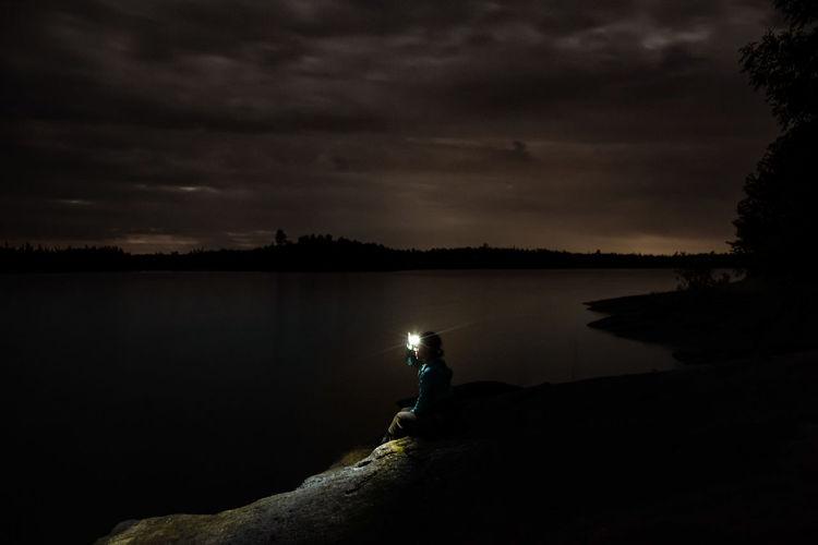 Man looking at lake against sky
