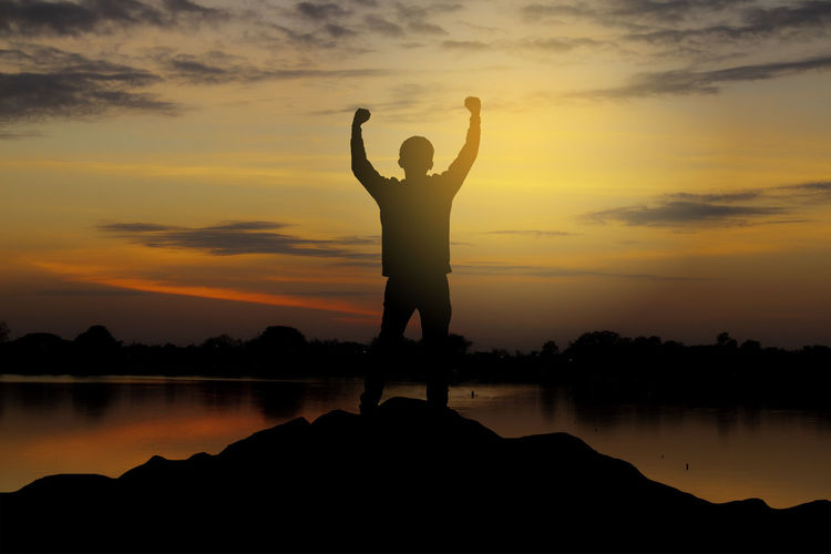silhouette of a happy man raised hands up as a successful, victory and achieve a business goal.