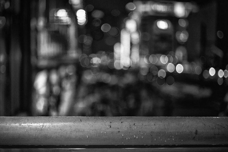 Defocused image of illuminated city street during rainy season