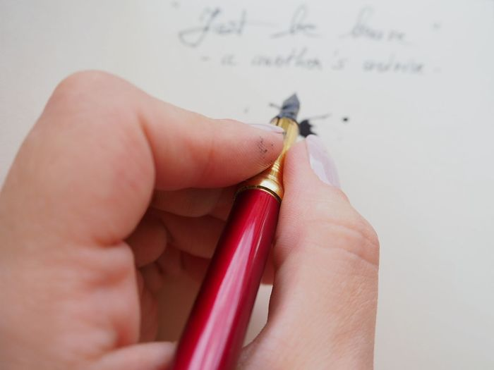 Cropped hand of woman writing in paper with calligraphy pen