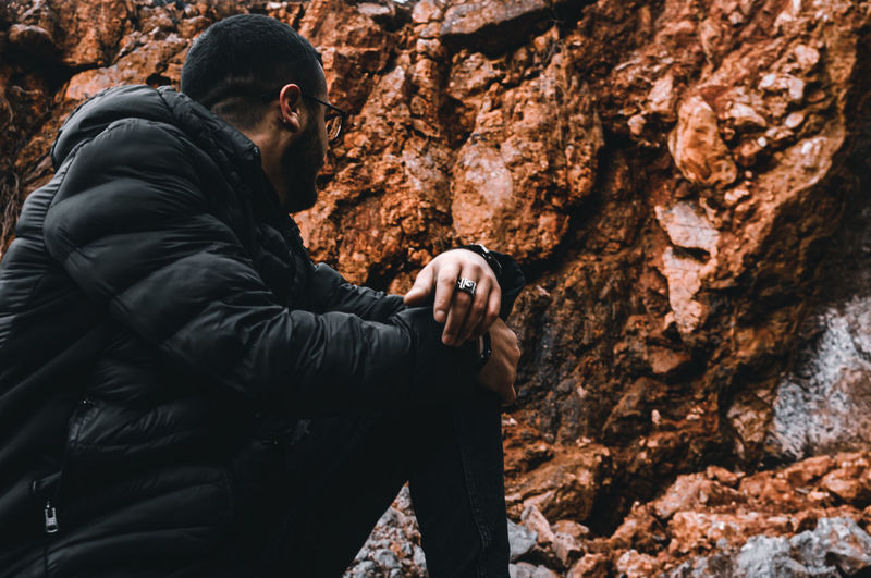 Side view of young man holding rock