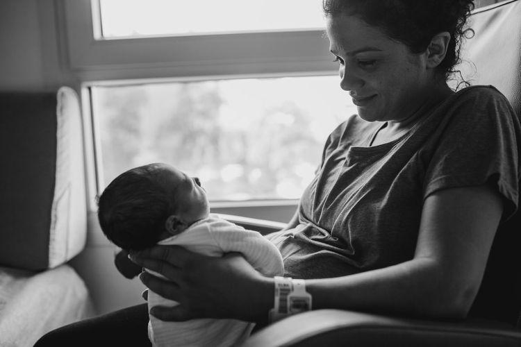 Woman holding newborn son in hospital