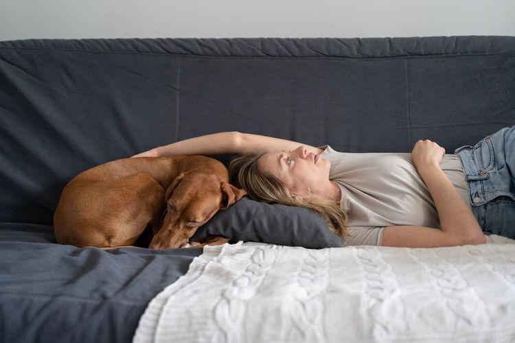 Woman with dog sleeping on sofa