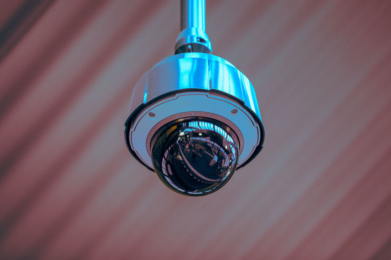 Low Angle View Of Security Camera Hanging From Ceiling
