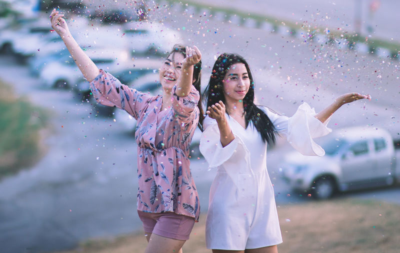 Playful Young Women Throwing Confetti In Park