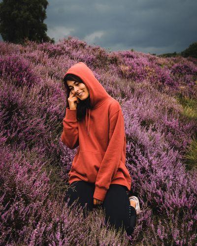 Woman standing on pink flowering plants on field