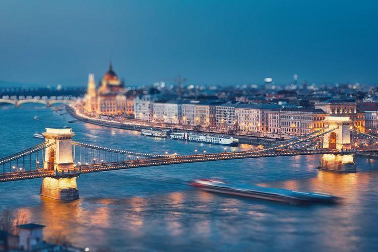 Bridge over river in illuminated city at night
