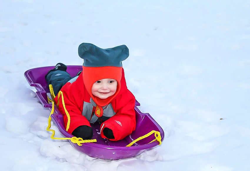 Child Childhood Snow Sports Ski Slope Gear Snowy Hills Snow Resort Snow Sledding Ski Resort  Children Playing Holding On Tight Sled Sledding Red Sleigh Tobogan Toboggan Tobogganing Snow Snow Covered Cap Winter Clothes Outerwear Ski Resort  Playing Red Hat