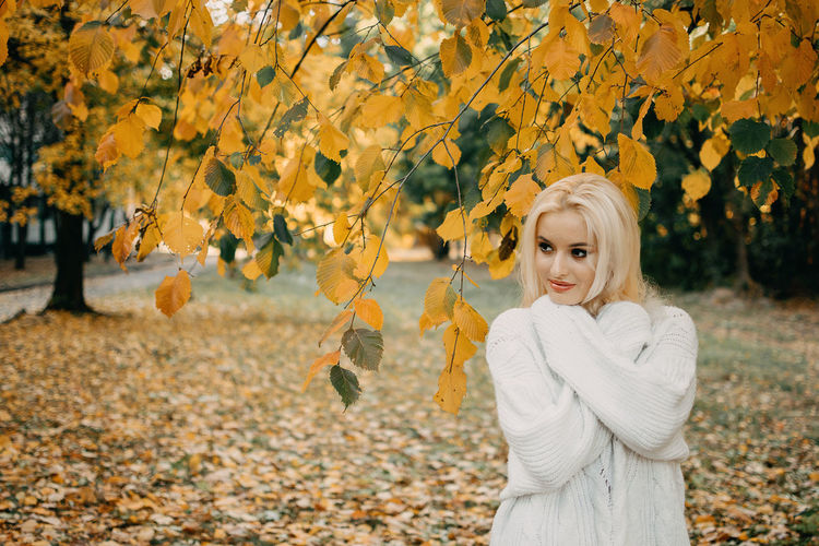 Beautiful blonde woman with autumn leaves on fall nature background. alone brooding woman in white