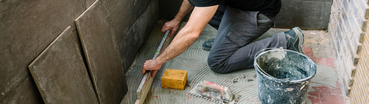 Low section of man working on cement